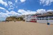 Playa de arena entre acantilados y en frente de la encantadora arquitectura blanca en Carvoeiro, Algarve, Portugal