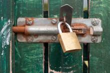 A Padlock On A Green Gate