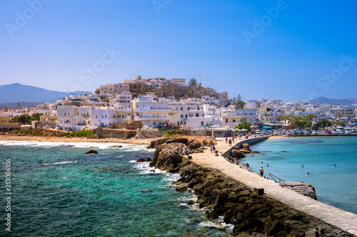 Платно Chora of Naxos island as seen from the famous landmark the Portara with the natural stone walkway towards the village, Cyclades, Greece
