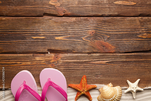 Fotografia  Shell, starfish, sand and flip flops on wooden board