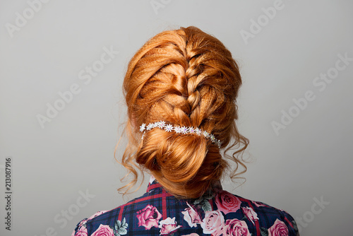 A female hairstyle is a low bun on a red-haired girl back view on a gray isolate Poster