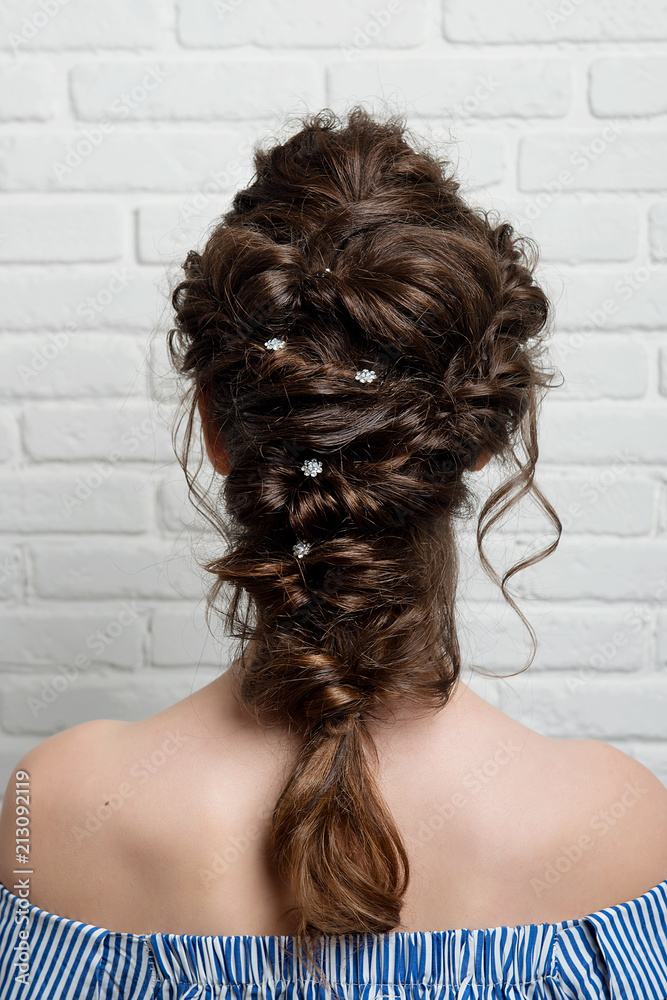 Fototapeta Female hairstyle Greek braid on the head of a brunette rear view.