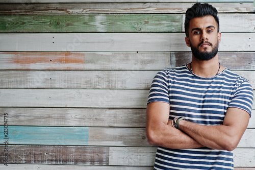Photo Handsome tall arabian beard man model at stripped shirt posed outdoor against wooden background