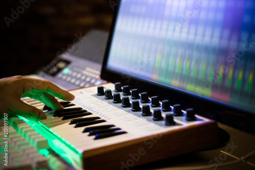 composer hands playing midi keyboard for recording song on computer in home studio - 213097307