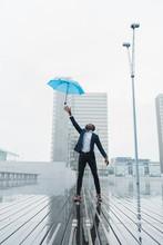 Ethnic Man Catching Umbrella S...