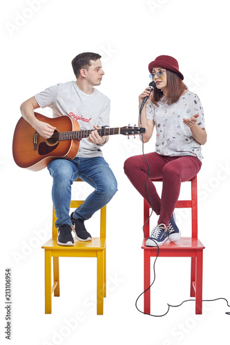 Young beautiful girl singing with a guitar player. Poster
