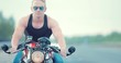 Large portrait of a biker on a motorcycle. Motorcyclist rides on the road. Portrait