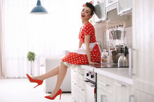 Funny Young Housewife Sitting On Kitchen Counter