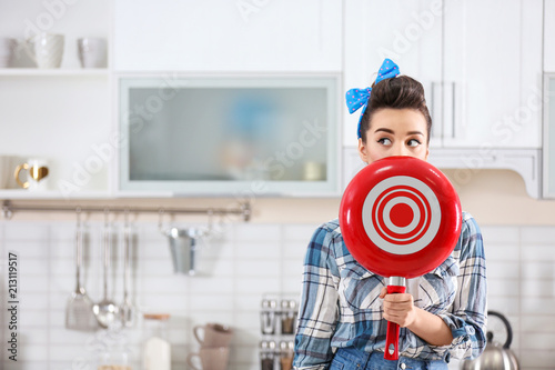 Fototapeta Funny young housewife with frying pan in kitchen obraz