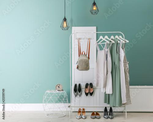 Fényképezés Stylish dressing room interior with clothes on rack