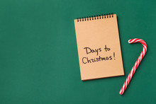 Notebook And Candy Cane On Color Background, Top View. Christmas Countdown