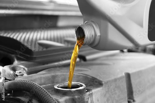 Fotografía  Pouring oil into car engine, closeup