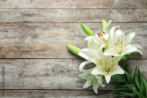 Flat lay composition with beautiful blooming lily flowers on wooden background Canvas Print