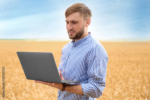 Photo Young agronomist with laptop in grain field. Cereal farming