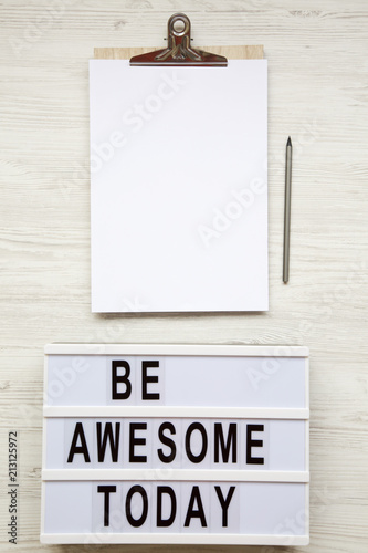 Poster  Work space with noticepad, pencil and 'Be awesome today' word on lightbox over white wooden background, top view