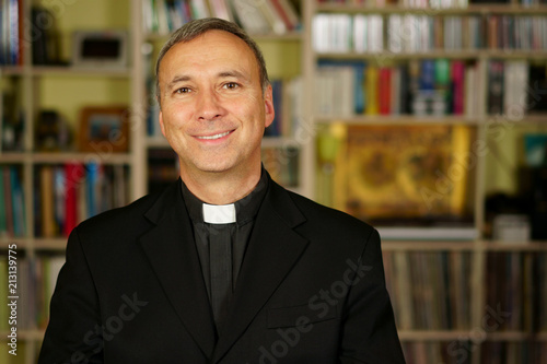Fototapeta A good looking catholic priest is studying into his library