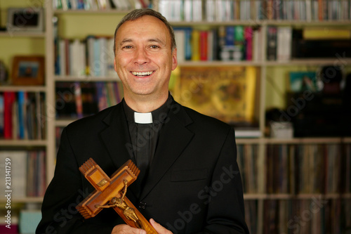 A good looking smiling and laughing catholic priest is showing a crucifix Fototapeta