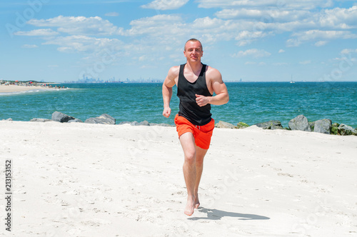 Fotografie, Obraz  Workout. Athletic man running on beach.