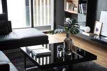 Cozy Black Glass Coffee Table Setting With Artificial Plants Compose With White Book