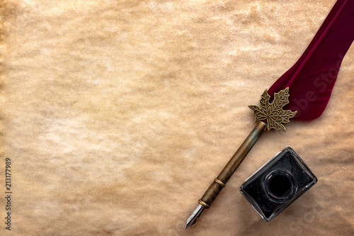 Calligraphy, literature and creative writing concept with a feather quill pen and black ink bottle on old yellowed paper or papyrus with copy space