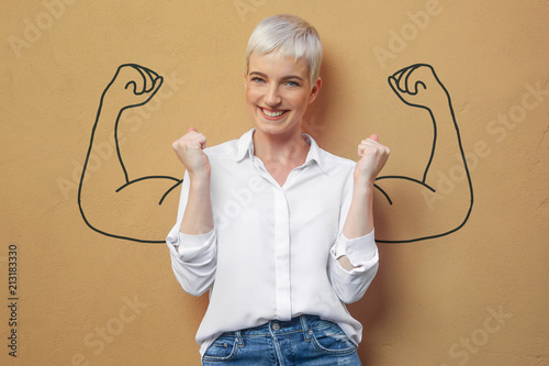 Fotomural Blond Frau an der Wand / Muskeln / Kraft / Power