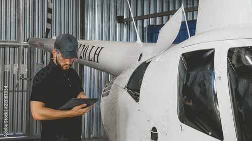 Male mechanic in uniform examining helicopter. Pre flight inspection at the airportы