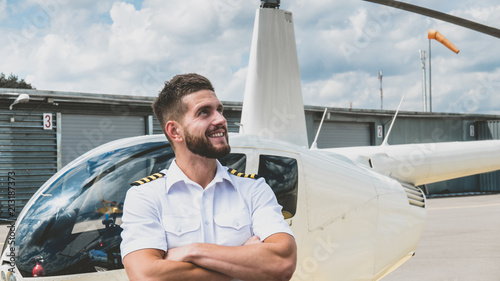 Fényképezés Portrait of commercial pilot in uniform standing near small private helicopter o