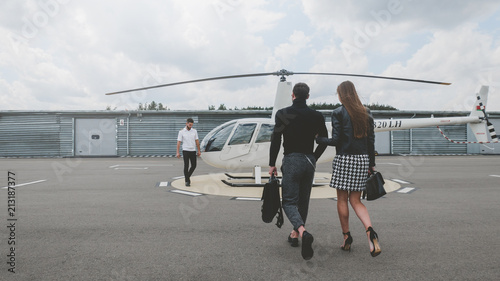 Fotografia Commercial pilot in uniform greeting clients near small private helicopter on a