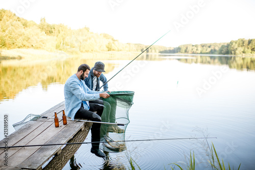 Fotobehang Vissen Two happy male friends looking at the fishing net with fish during the fishing on the lake