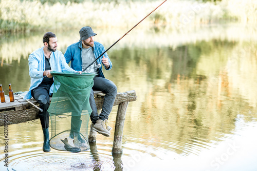 Spoed Fotobehang Vissen Two happy male friends looking at the fishing net with fish during the fishing on the lake