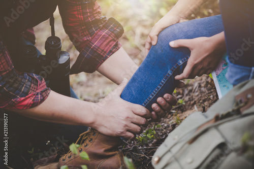 Fotomural  Asian young couple travelers to hiking  ankle injury on a green background, Hiking concept