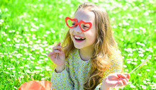 Love From First Sight Concept. Child Posing With Cardboard Heart Shaped Eyeglasses. Girl On Happy Face Spend Leisure Outdoors. Girl Sits On Grass At Grassplot, Green Background.