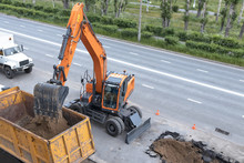 Excavator Digs A Hole On The Road In The City. Repair Of Pipelines