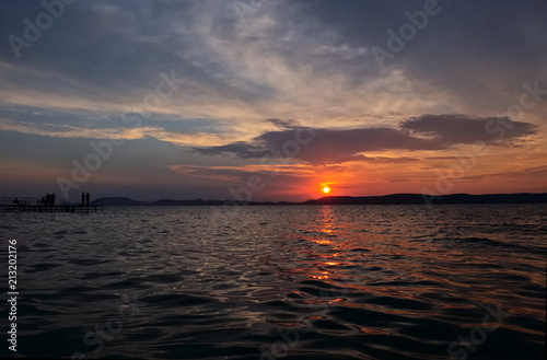 Spoed Foto op Canvas Zee zonsondergang sunset over lake Balaton, angling men silhouette - golden bridge, calm water, close up, hills in background