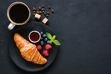 Croissant, Fresh Berries, Jam And Cup Of Black Coffee On Black Background. Top View, Copy Space For Text