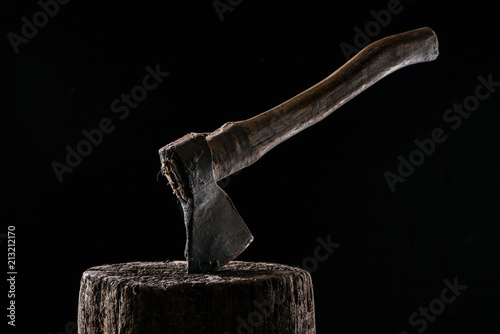 close up view of vintage axe on wooden stump isolated on black Canvas Print