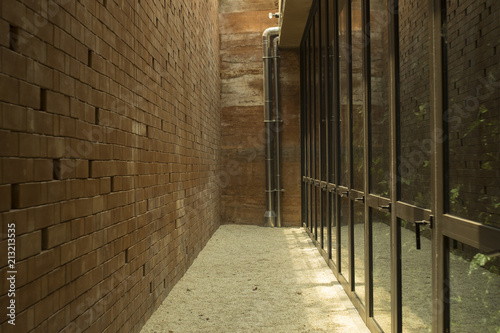 Fototapeten Schmale Gasse Background and texture of alleyway. Space between the brown brick wall and glass window.