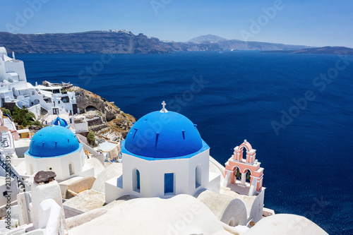 Blue rooftops in city Fira, Santorini, Greece, overlooking the deep blue sea.