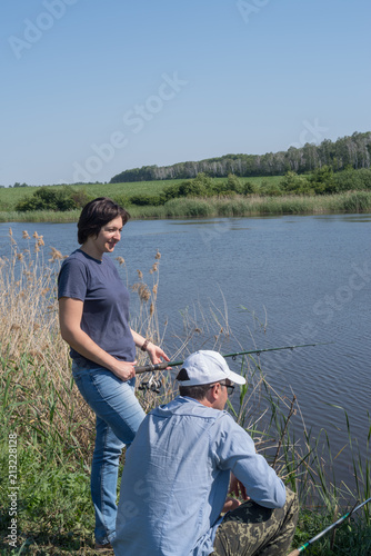 Printed kitchen splashbacks Fishing Couple woman and man fishing standing on lake shore