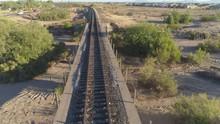 4K Aerial Of Desert Train Bridge At Sunrise Near Development