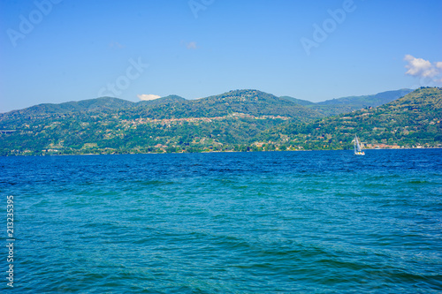 Spoed Foto op Canvas Eiland panorama of Lake Maggiore, Verbano, summer day with sun and sailing boat sailing on the horizon