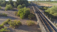 4K Aerial Of Desert Train Tracks Beside Highway At Sunrise