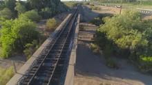 4K Aerial Of Desert Train Bridge By Highway At Sunrise