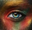 Leinwandbild Motiv Macro and close-up creative make-up theme: beautiful female eye with yellow, orange and green paint on black skin, space and stars