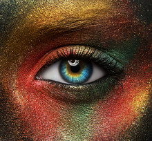 Macro And Close-up Creative Make-up Theme: Beautiful Female Eye With Yellow, Orange And Green Paint On Black Skin, Space And Stars