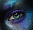 Macro and close-up creative make-up theme: beautiful female eye with blue and purple paint on black skin, space and stars