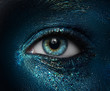 Macro and close-up creative make-up theme: beautiful female eyes with black skin with a blue-green pigment sparkles