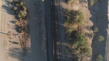 4K Aerial Slow Descent Of Desert Train Tracks At Sunrise