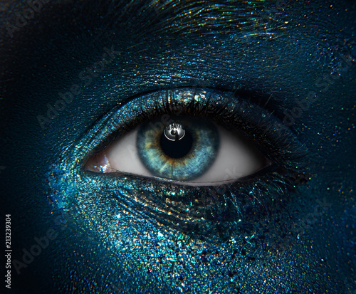 Türaufkleber Makrofotografie Macro and close-up creative make-up theme: beautiful female eyes with black skin with a blue-green pigment sparkles