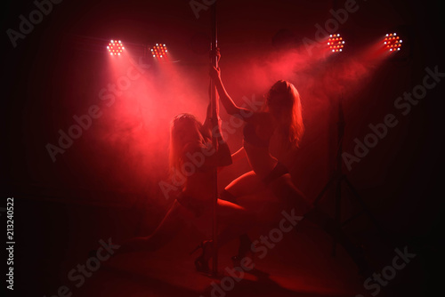 Two young girls doing acrobatic tricks with a pole - fototapety na wymiar